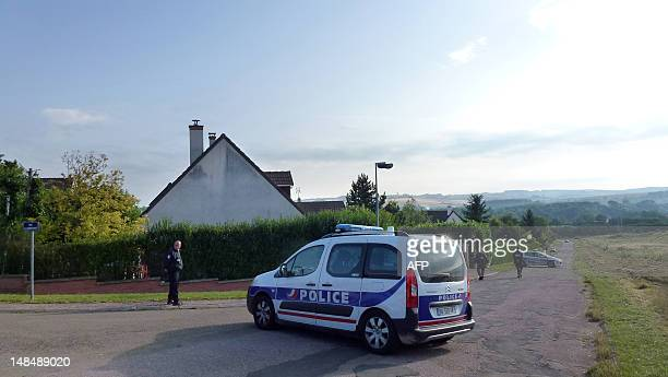 French policemen stand next to a house where five persons were found dead on July 18 2012 in Auxerre Burgundy A family man who was found hanged...