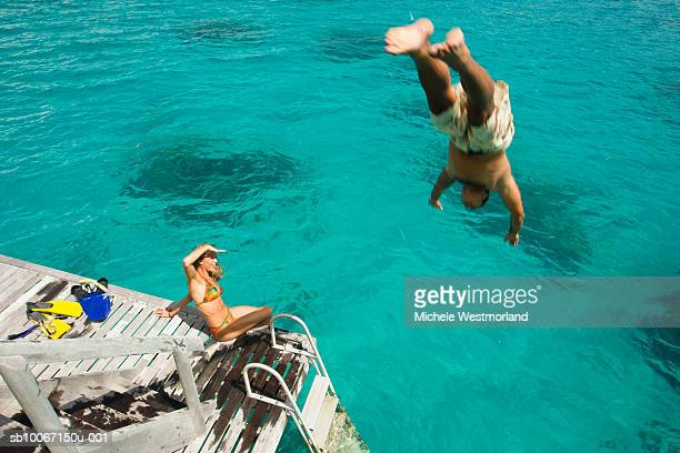 French Polynesia, Bora Bora, Bora Bora Nui Resort, Man diving into water, woman watching, elevated view