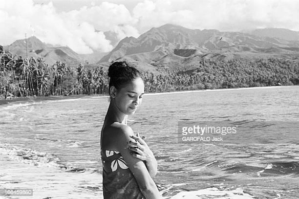 French Polynesia Le 29 décembre 1959 à Tahiti en Polynésie française l'ile au quotidien une femme en paréo devant la montagne les palmiers et la mer