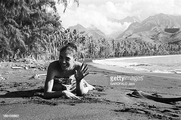 French Polynesia Le 29 décembre 1959 à Tahiti en Polynésie française l'ile au quotidien une femme en paréo couchée sur le sable saluant l'objectif...