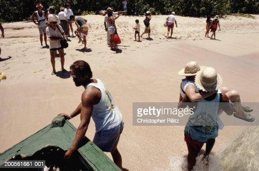 French Polynesia, passengers disembarking boat onto beach : Stock Photo