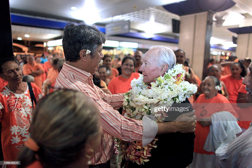 French Polynesia senator Gaston Flosse (center) is welcomed by supporters late on November 22, 2012 in Pirea, after his return from New Zealand, where he applied for a visa for the United States. Flosse, who house was destroyed by a fire on November 19, said the fire was arson.