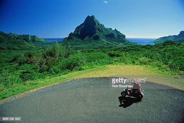 French Polynesia,Moorea,Roto Nui, couple on scooter on coast road