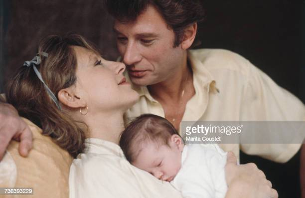 French pop singer and actor Johnny Hallyday with French actress Nathalie Baye and their newborn daughter Laura Paris 15th November 1983