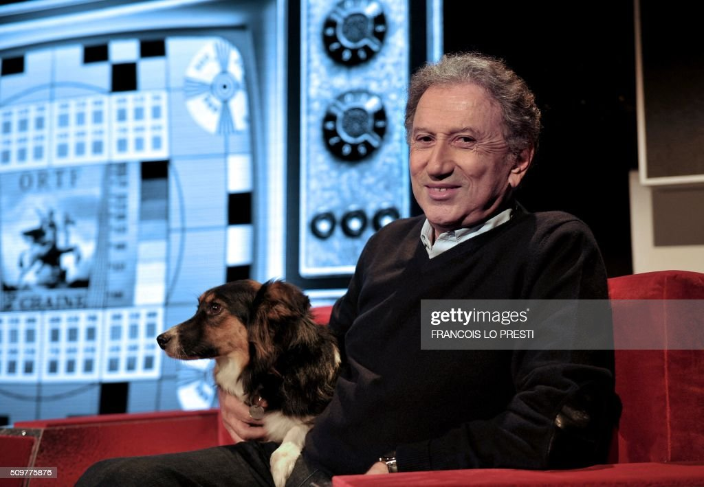 French presenter Michel Drucker poses with his dog Izia on stage before his one-man show at the Zenith in Amiens, northern France, on February 12, 2016. / AFP / FRANCOIS LO PRESTI