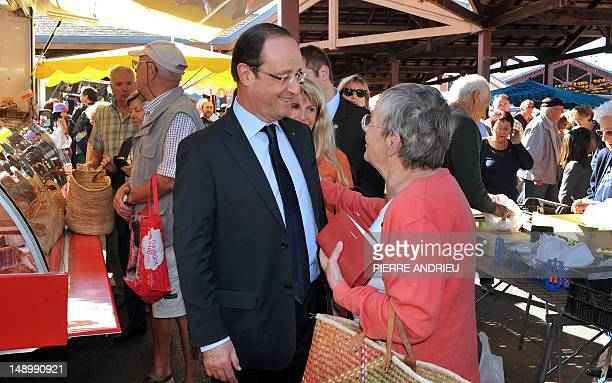 French President and former Socialist President of the Correze department General Council Francois Hollande speaks with a woman during a visit at the...