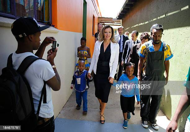 French president companion Valerie Trierweiler walks with children during a visit to the Soweto Kliptown Youth Centre in Soweto on October 15 2013...