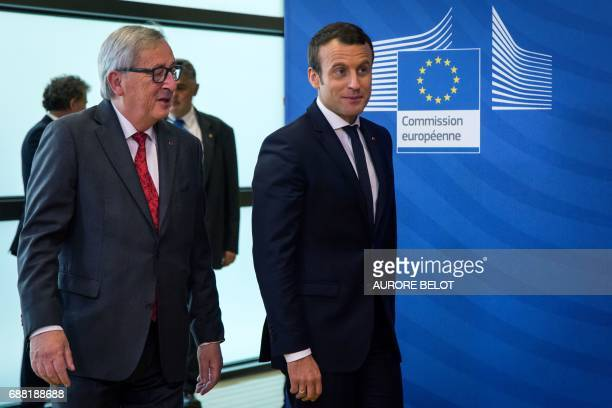 French President Emmanuel Macron and European Commission President JeanClaude Juncker walk during their meeting at the European Commission...