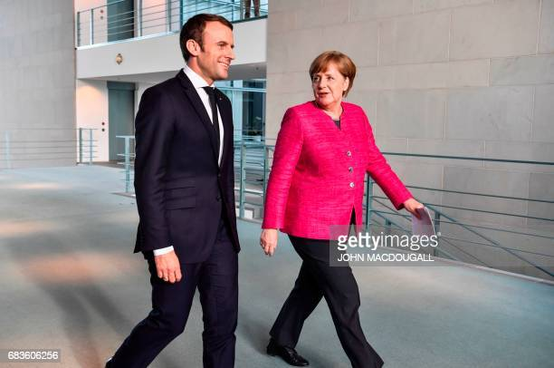 French President Emmanuel Macron and German Chancellor Angela Merkel arrive for a press conference following talks at the Chancellery in Berlin on...