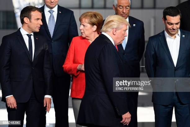 French President Emmanuel Macron and German Chancellor Angela Merkel speaks as US President Donald Trump arrives next to Greek Prime Minister Alexis...