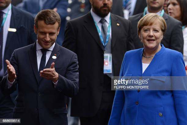French President Emmanuel Macron and German Chancellor Angela Merkel walk to the Hotel San Domenico during the Summit of the Heads of State and of...
