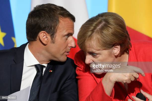 French President Emmanuel Macron and German Chancellor Angela Merkel attend a meeting with EU and African leaders to discuss how to ease the European...