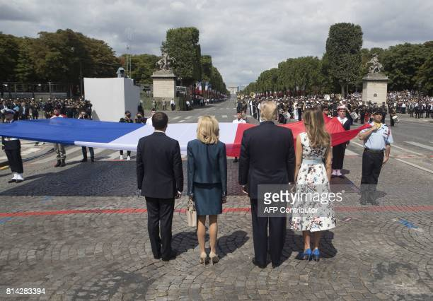 French President Emmanuel Macron and his wife Brigitte Macron and US President Donald Trump and First Lady Melania Trump stand in front of the French...