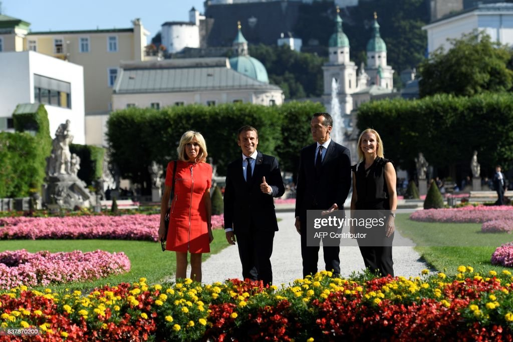 TOPSHOT - French President Emmanuel Macron (2ndL) and his wife Brigitte Macron (L) pose for a group photo with Austrian chancellor Christian Kern (2ndR) and his wife Eveline Steinberger-Kern on August 23, 2017 at Mirabell park in Salzburg. / AFP PHOTO / Bertrand GUAY / The erroneous mention[s] appearing in the metadata of this photo by Bertrand GUAY has been modified in AFP systems in the following manner: [Mirabell park] instead of [Mirabebell park]. Please immediately remove the erroneous mention[s] from all your online services and delete it (them) from your servers. If you have been authorized by AFP to distribute it (them) to third parties, please ensure that the same actions are carried out by them. Failure to promptly comply with these instructions will entail liability on your part for any continued or post notification usage. Therefore we thank you very much for all your attention and prompt action. We are sorry for the inconvenience this notification may cause and remain at your disposal for any further information you may require.