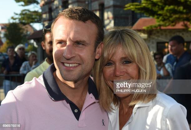 TOPSHOT French President Emmanuel Macron and his wife Brigitte Macron pose for photographers as they meet people in the street at Le Touquet northern...
