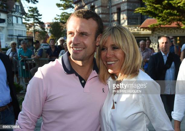 French President Emmanuel Macron and his wife Brigitte Macron pose for photographers as they meet people in the street at Le Touquet northern France...
