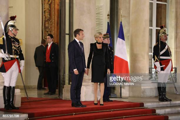 French President Emmanuel Macron and his wife Brigitte Macron wait for the arrival of Lebanon's President and his wife for a state dinner at the...
