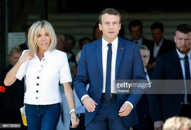 French President Emmanuel Macron and his wife Brigitte Trogneux leave the polling station of the town hall after casting their vote in the first...