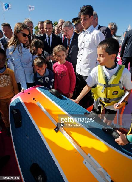 French President Emmanuel Macron and International Olympic Committee President Thomas Bach speak with children as they visit the site of the future...