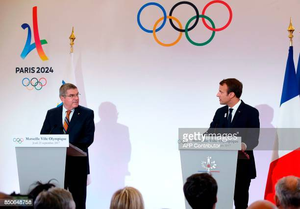French President Emmanuel Macron and International Olympic Committee President Thomas Bach hold a press conference during a visit to the site of the...