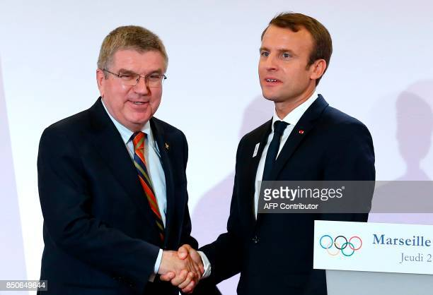 French President Emmanuel Macron and International Olympic Committee President Thomas Bach shake hands during press conference as part of a visit to...