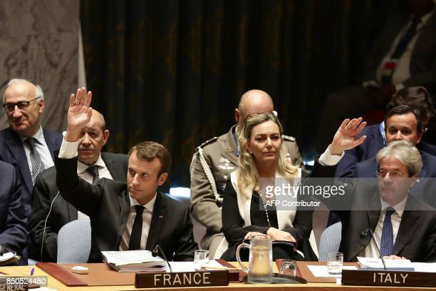 French President Emmanuel Macron and Italian Prime Minister Paolo Gentiloni raise their hands as they participate in an open debate of the United...