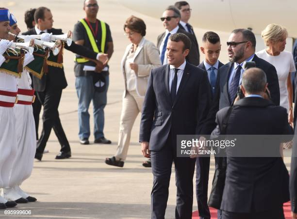 French President Emmanuel Macron and Moroccan King Mohammed VI walk during a welcome ceremony at the airport in Rabat on June 14 2017 Macron is on an...