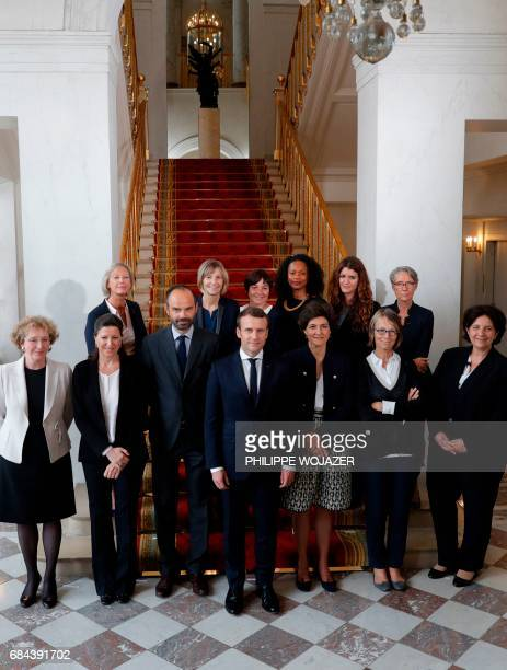 French President Emmanuel Macron and Prime Minister Edouard Philippe pose for a family photo with women ministers of the government after the first...