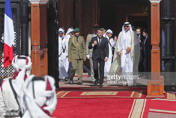 French President Emmanuel Macron and Qatari Emir Sheikh Tamim bin Hamad alThani review the honour guard during a welcome ceremony in the Qatari...