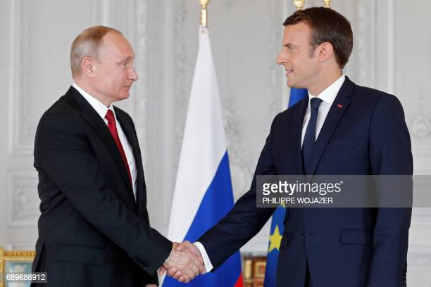 French President Emmanuel Macron and Russian President Vladimir Putin shake hands during their meeting at the Versailles Palace near Paris on May 29...
