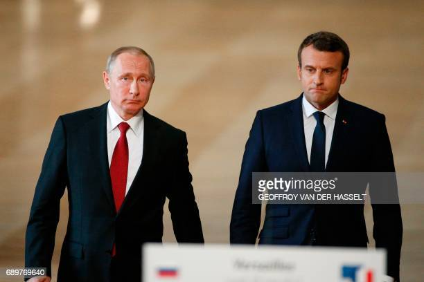 French President Emmanuel Macron and Russian President Vladimir Putin walk to deliver a joint press conference following their meeting at the...