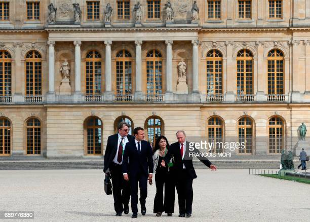 French President Emmanuel Macron and Russian President Vladimir Putin followed by their interpreters walk in the garden of the Versailles Palace...