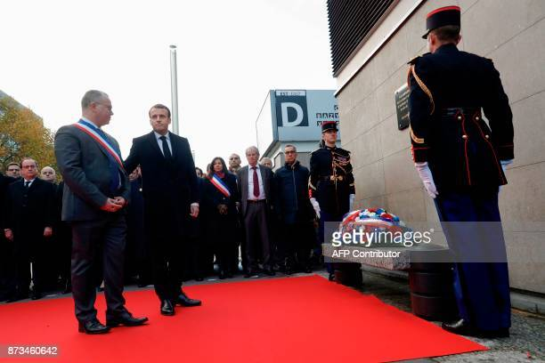 French President Emmanuel Macron and SaintDenis mayor Laurent Russier stand after they laid a wreath in front of a commemorative plaque outside the...