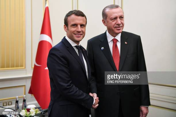 French President Emmanuel Macron and Turkish President Recep Tayyip Erdogan shake hands ahead of a meeting on the sidelines of the NATO summit in...