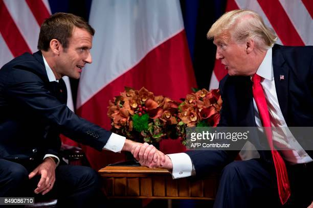 TOPSHOT French President Emmanuel Macron and US President Donald Trump shake hands before a meeting at the Palace Hotel during the 72nd session of...