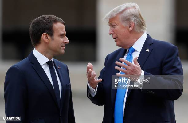 French President Emmanuel Macron and US President Donald Trump talk during a welcome ceremony at Les Invalides in Paris on July 13 as part of a...