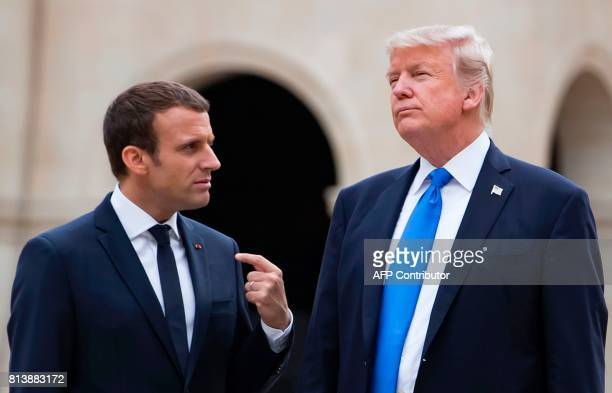 TOPSHOT French President Emmanuel Macron and US President Donald Trump talk as they leave the Army Museum at Les Invalides in Paris on July 13 during...