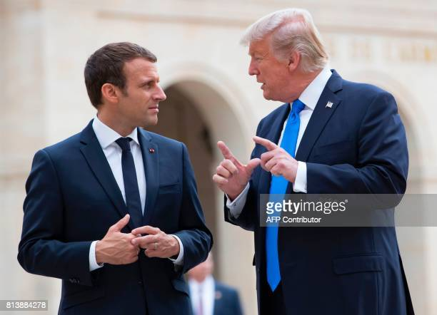 French President Emmanuel Macron and US President Donald Trump talk as they leave the Army Museum at Les Invalides in Paris on July 13 during Trump's...