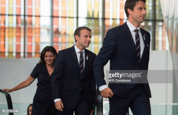 French President Emmanuel Macron arrives flanked by Paris Mayor Anne Hidalgo and Paris 2024 Olympic bid copresident Tony Estanguet prior to present...