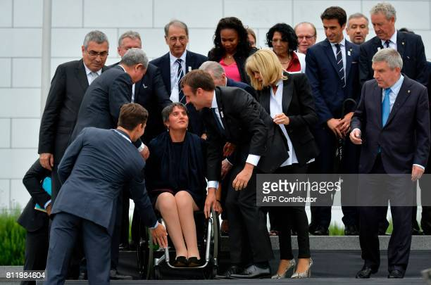 French President Emmanuel Macron assists President of The French Paralympic Committee Emmanuelle Assmann as French President's wife Brigitte Macron...