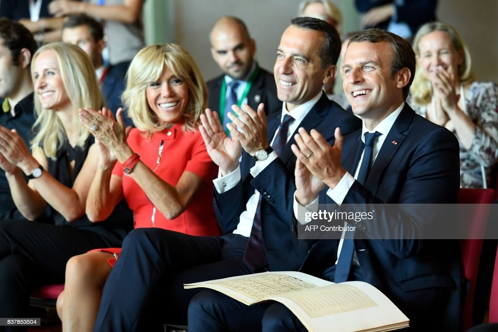 French President Emmanuel Macron, Austrian Chancellor Christian Kern applaud with their wifes Brigitte Macron and Eveline Steinberger-Kern during a piano masterclass by French pianist Dominique Merlet on August 23, 2017 at the Mozarteum university in Salzburg, Austria. / AFP PHOTO / POOL / Bertrand GUAY