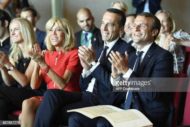 French President Emmanuel Macron Austrian Chancellor Christian Kern applaud with their wifes Brigitte Macron and Eveline SteinbergerKern during a...