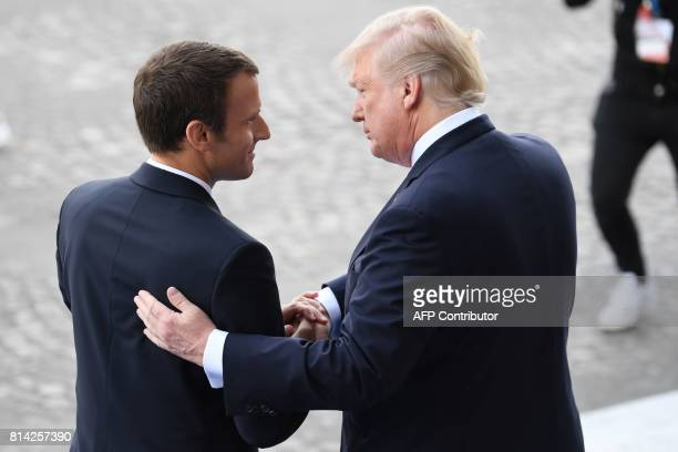 TOPSHOT French President Emmanuel Macron bids farewell to his US counterpart Donald Trump after the annual Bastille Day military parade on the...