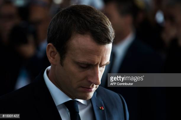 French President Emmanuel Macron bows his head as he pays his respects after laying a wreath during a ceremony commemorating the 75th anniversary of...