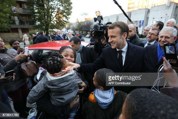 French President Emmanuel Macron caresses the face of a child as he arrives at the Cite du Chene pointu in ClichysousBois northern Paris on November...