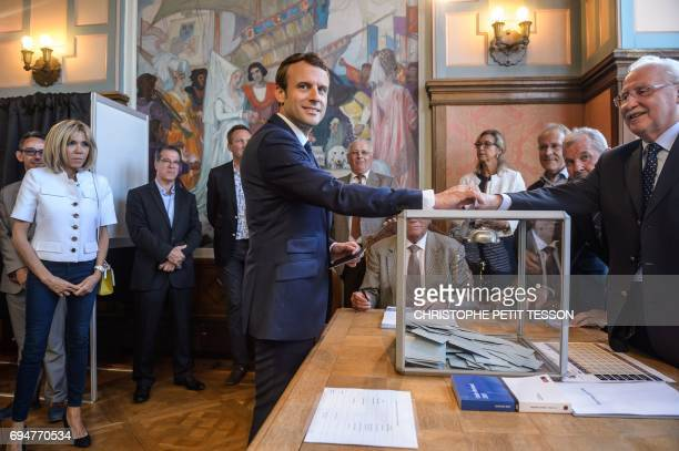 TOPSHOT French President Emmanuel Macron casts his ballot next to his wife Brigitte Macron at a polling station during the first round of the French...