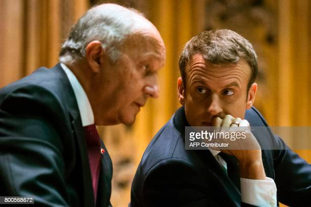 French President Emmanuel Macron confers with former French Foreign Minister Laurent Fabius during the World Environment Pact meeting at the Sorbonne...