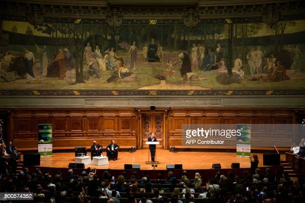 French President Emmanuel Macron delivers a speech as former French Foreign Minister Laurent Fabius as former UN SecretaryGeneral Ban Kimoon look on...