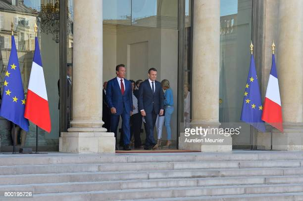 French President Emmanuel Macron escorts Arnold Schwarzenegger out after a meeting at the Elysee Palace on June 23 2017 in Paris France On their...