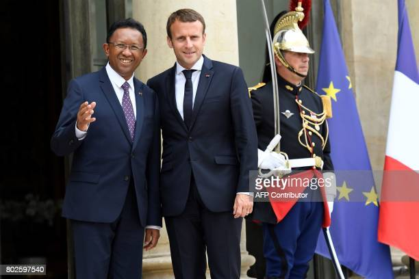 French President Emmanuel Macron escorts his Madagascar counterpart Hery Rajaonarimampianina as he leaves following their meeting at the Elysee...